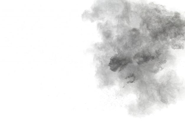 Schwarzpulver-explosion auf weißem hintergrund. schwarze staubpartikel spritzen.
