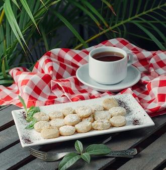 Schwarztee serviert mit einer platte mit runden kleinen keksen mit puderzucker
