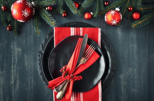 Schwarzteller und vintage-besteck mit weihnachtsschmuck in grün und rot