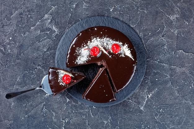 Schwarzwälder schokoladenkuchen mit kirschfüllung mit dunkler schokoladenglasur auf der oberseite verziert mit eingemachten kirschen und weißer schokolade