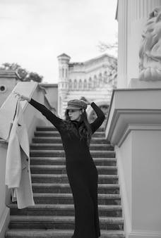 Schwarzweiss-bild eines jungen weiblichen modells, gekleidet in ein enges schwarzes kleid, das flirtet und ihren mantel in der hand hält, nahe der treppe eines gebäudes. vertikale ansicht.