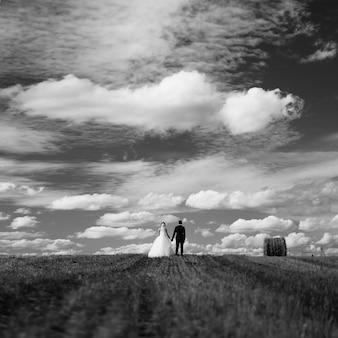 Schwarzweiss-foto der romantischen hochzeit von silhouetten von braut und bräutigam im feld mit garben und einem schönen bewölkten himmel