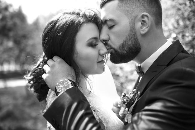 Schwarzweiss-foto. junges hochzeitspaar, das romantische momente draußen auf einer sommerwiese genießt