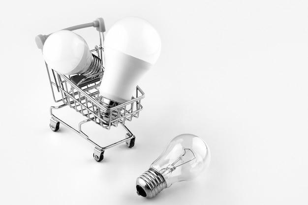 Schwarzweiss-foto. konzept der modernen wirtschaftlichen beleuchtung. energiesparlampen werden in einen korb auf rädern gelegt.
