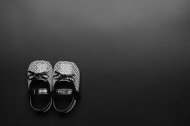 Schwarzweiss-kinderbabyschuhe auf schwarzem hintergrund