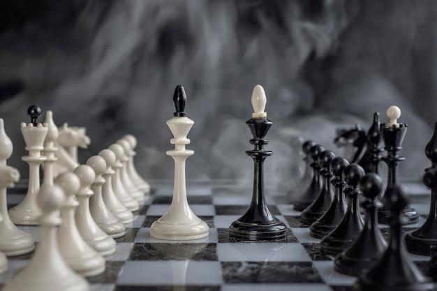 Schwarzweiss-könige der schacheinrichtung auf dunklem hintergrund.