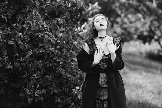 Schwarzweiss-kunstfotografie monochrom, mädchen im mantel, das auf einem hintergrund eines busches mit rosen aufwirft. ring an einem finger. lange haare. blasse haut. anhänger am hals.