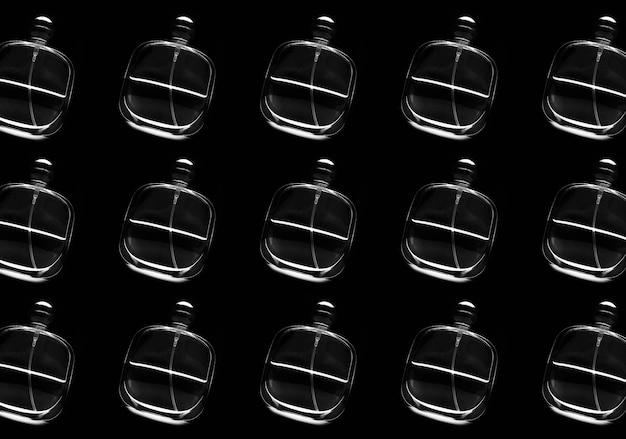 Schwarzweiss-muster von glasparfümflaschen auf schwarzem hintergrund.