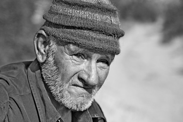 Schwarzweiss-nahaufnahme des alten armenischen mannes, der im landwirtschaftlichen feld steht