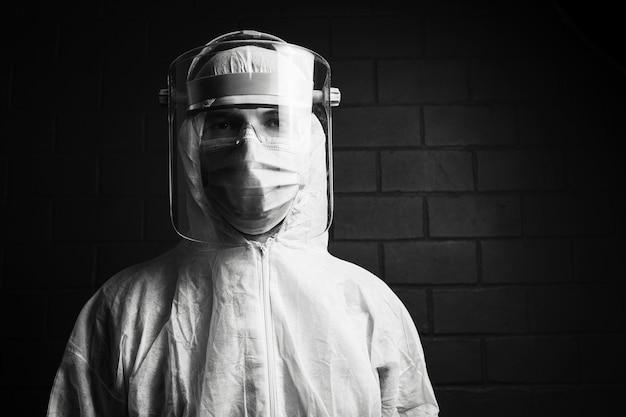 Schwarzweiss-porträt eines arztes, der psa-anzug gegen coronavirus und covid-19 trägt