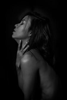 Schwarzweiss-portrait des reizvollen mädchens. erotische schöne frau in der dunkelheit