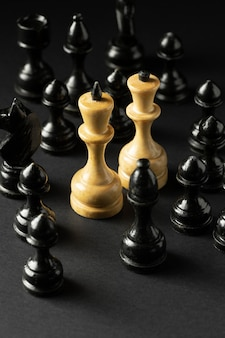 Schwarzweiss-schachfiguren auf schwarzem hintergrund