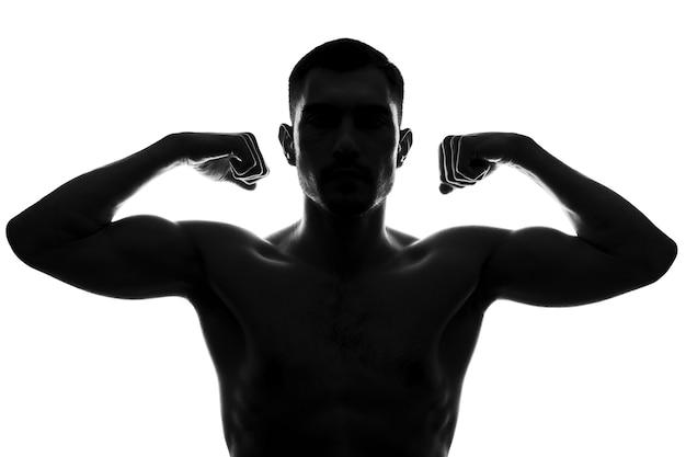 Schwarzweiss-silhouette, frontalporträt eines mannes zeigt bizeps auf armen mit nacktem oberkörper