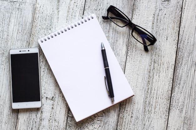 Schwarzweiss-stillleben: geöffneter leerer notizblock, notizbücher, stift, bleistift, gläser, geldbeutel.