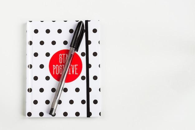 Schwarzweiss-tupfenanmerkungsbuch mit rotem kreis auf der abdeckung und schwarzem stift auf weißer tabelle. draufsicht, minimale flachlage
