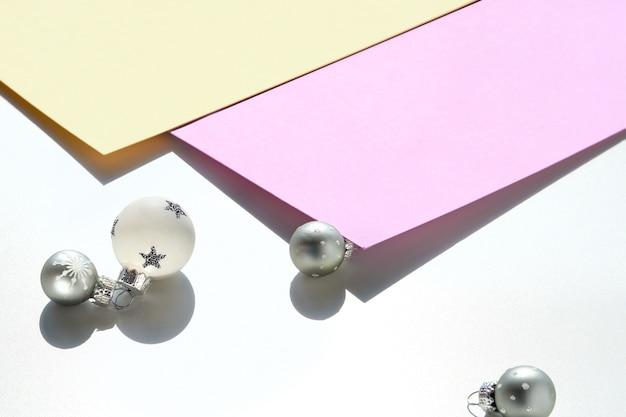 Schwarzweiße weihnachtskugeln auf geschichtetem farbpapier
