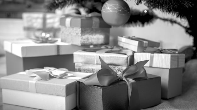 Schwarzweißes entsättigtes bild von weihnachtsgeschenken in schachteln mit band unter dem weihnachtsbaumzweig mit hängenden kugeln