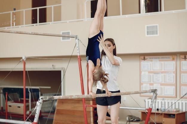 Schwebebalken für kindergymnastik. mädchengymnastathlet während einer übungshorizontalstange in turnwettbewerben. coach mit kind.