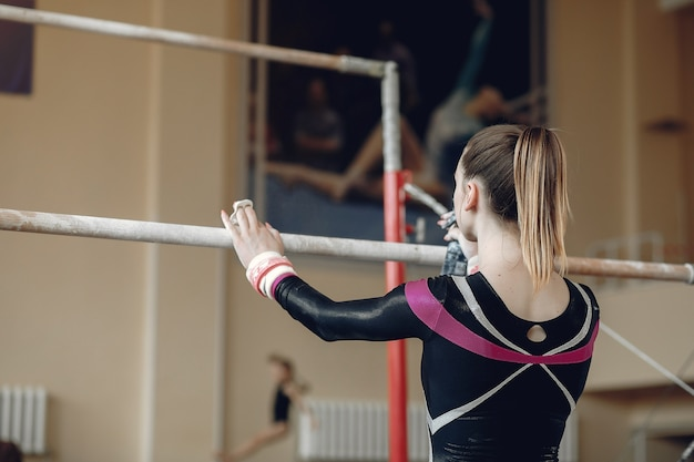 Schwebebalken für kindergymnastik. sportlerin des turners während einer horizontalen übungsstange in turnwettbewerben.
