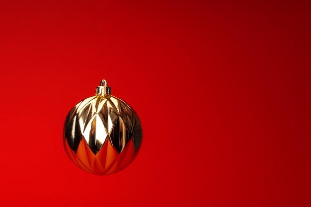 Schweben im luftweihnachtsflitter über rotem hintergrund. weihnachtskarte