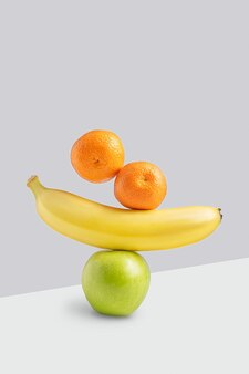 Schwebende oder ausgleichende reife orangen-mandarinen-zitrusfrüchte, gelbe süße bananen und grüne saure äpfel