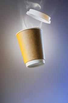 Schwebende pappbecher mit heißem kaffee
