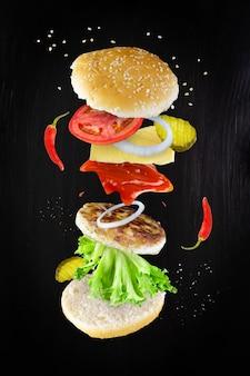 Schwebende würzige cheeseburger-zutaten an der dunklen wand. in der luft schwebende burger-komponenten: paprika, gurken, käse, ketchup, zwiebel, schnitzel, tomate, salat, ketchup.