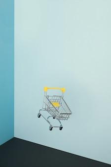 Schwebender einkaufswagen auf blauem hintergrund