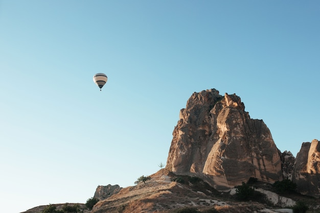 Schwebender heißluftballon über den bergen von kappadokien
