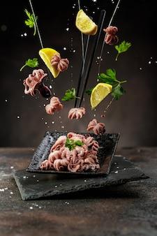 Schwebendes oder fliegendes lebensmittelkonzept. traditionelles japanisches essen. mini gekochter ocopus, zitronen, salz und petersilie mit stäbchen, die über dem schwarzen grounge-tisch fliegen.