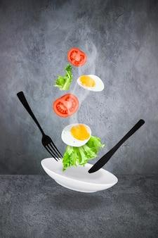 Schwebendes rührei mit dampf, tomatenscheiben, salat, weißer teller, schwarze gabel und messer auf grauem hintergrund