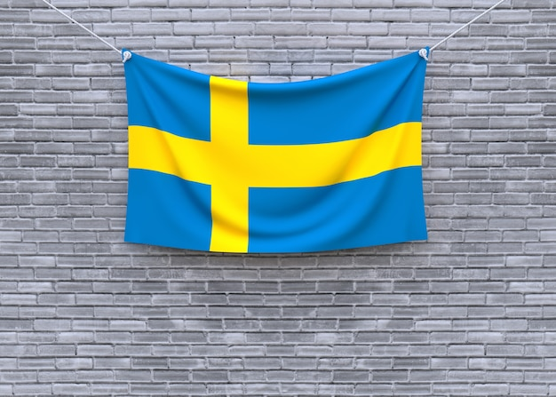 Schweden-flagge, die an der backsteinmauer hängt