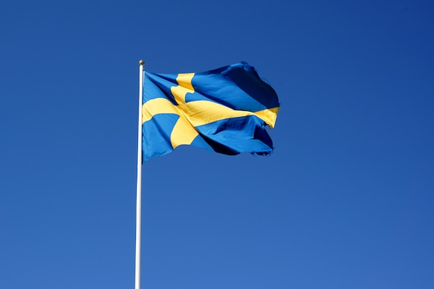 Schwedenflagge, die gegen den klaren blauen himmel weht