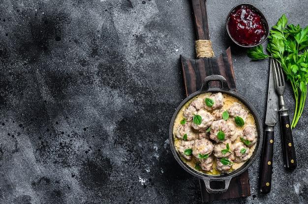 Schwedische fleischbällchen mit preiselbeersauce in einer pfanne. schwarzer hintergrund