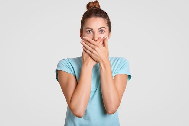 Schweigen sie bitte. die verängstigte frau bedeckt den mund mit beiden handflächen, schaut mit verängstigtem gesichtsausdruck direkt in die kamera, trägt ein lässiges t-shirt und hält informationen geheim. sprich kein böses konzept.