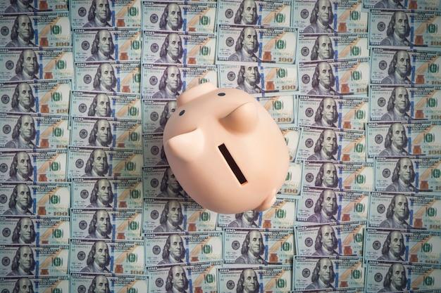 Schwein sparschwein auf dem hintergrund von 100 us-dollar-scheinen. konzept von reichtum und austausch. ansicht von oben