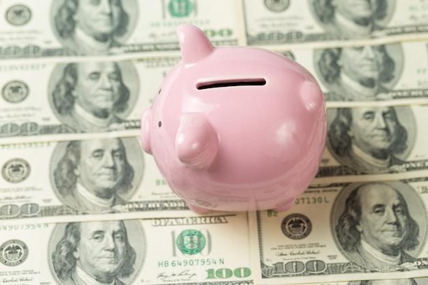Schwein sparschwein auf dem hintergrund von 100 us-dollar-scheinen und physischen bitcoin-münzen