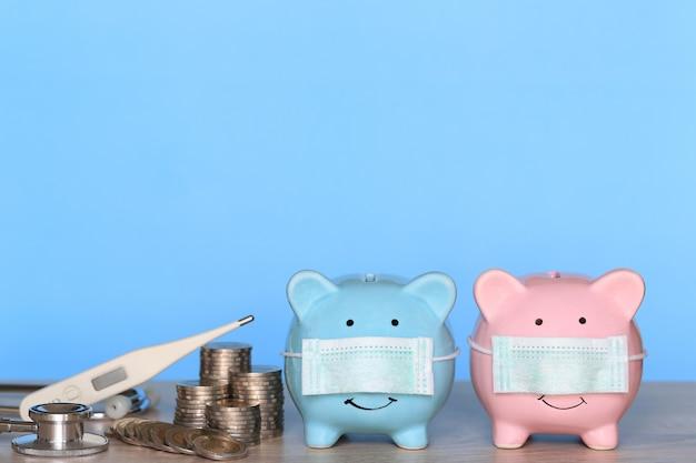 Schweinchen mit tragender medizinischer schutzmaske und thermometer mit stapel von geldmünzen auf hölzernem hintergrund, geld sparen für krankenversicherung und gesundheitskonzept