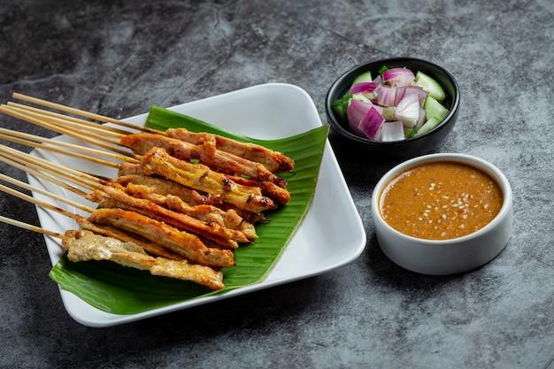 Schweine-satay mit erdnusssauce oder süß-saurer sauce, thailändisches essen