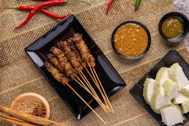 Schweine-satay oder sate babi schweine-satay serviert mit einer erdnusssauce und scheiben von lontong- oder ketupat-reiskuchen