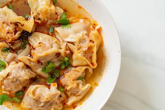 Schweine-wan-tan-suppe oder schweine-knödel-suppe mit geröstetem chili - asiatische küche