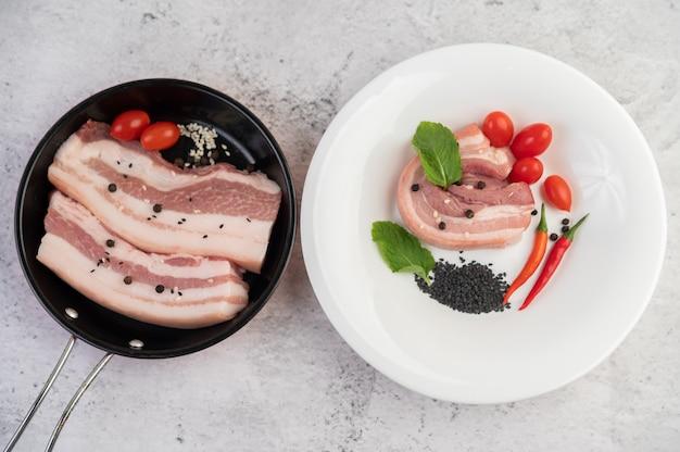 Schweinebauch in einer pfanne mit pfeffersamen tomaten und gewürzen