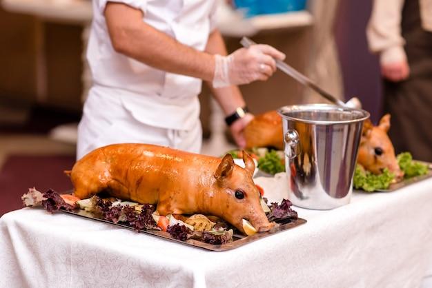 Schweinebraten. gebratenes ferkel mit gemüse auf servierplatte