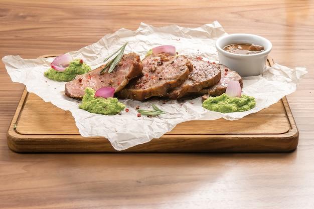 Schweinebratenstücke mit gewürzen, rosmarin, erbsenpüree und sauce auf einem holztisch