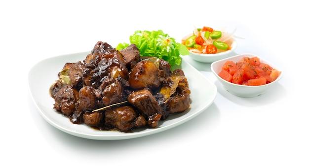Schweinefleisch adobo karamellisiertes philippinisches gericht, hinzugefügt mit dem beliebten gericht mit süßem und saurem geschmack auf den philippinen. asean foods serviert in der seitenansicht von gericht und gemüse