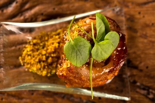 Schweinefleisch ballotine mit pururuca, wassermehl, kürbispüree und sprossen in einem löffel. probieren sie gastronomisches fingerfood