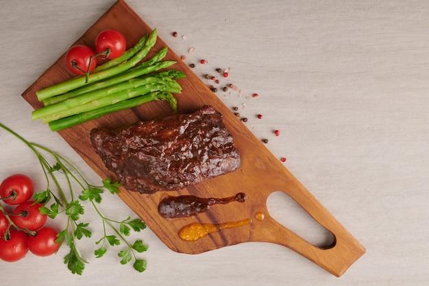 Schweinefleisch gebratene, gegrillte spareribs von einem sommergrill, serviert mit gemüse, spargel, babykarotten, frischen tomaten und gewürzen. geräucherte rippen auf holzschneidebrett auf steinoberfläche. draufsicht.