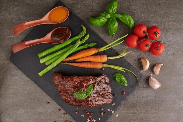 Schweinefleisch gebratene, gegrillte spareribs von einem sommergrill, serviert mit gemüse, spargel, babykarotten, frischen tomaten und gewürzen. geräucherte rippen auf schwarzer steinoberfläche. draufsicht,