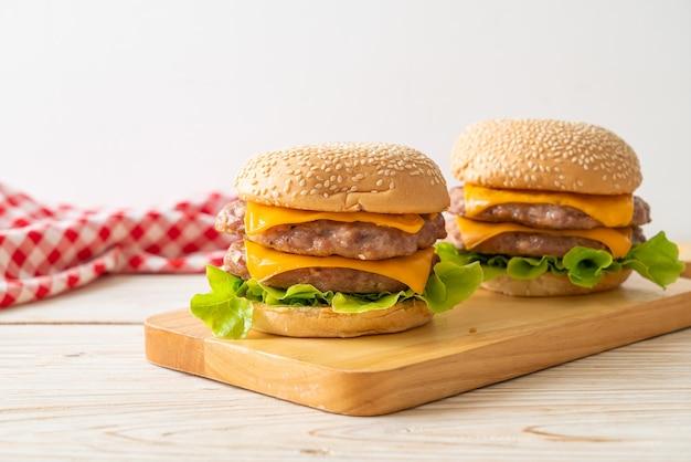 Schweinefleisch-hamburger oder schweinefleisch-burger mit käse auf holzbrett