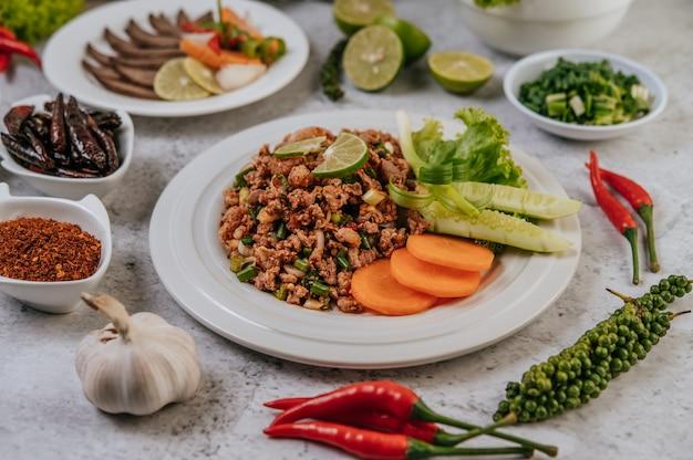 Schweinefleisch larb mit karotten, gurken, limetten, frühlingszwiebeln, chili, frisch gemahlenem pfeffer und salat.